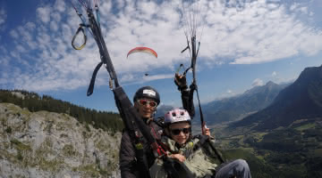 enfant en parapente avec pilote, ciel bleu et nuages